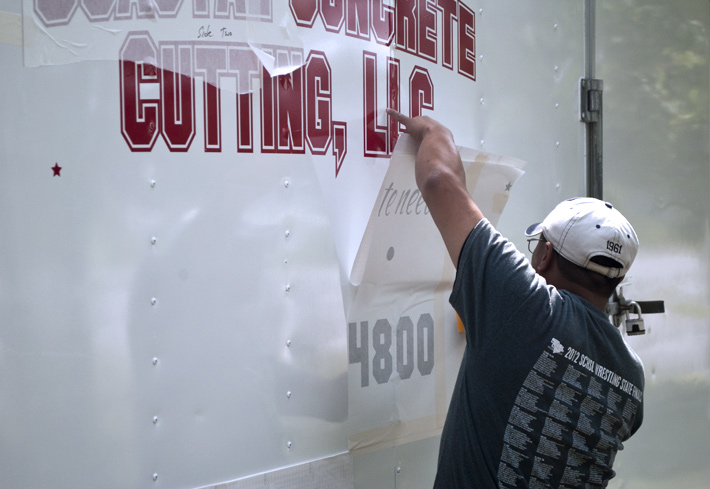 A photo of vinyl lettering and graphics being applied to a vehicle
